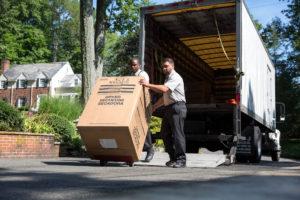foto due due ragazzi che scaricano uno scatolone da un camion