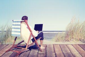 foto di un ragazzo seduto su uno sdraio in riva al mare mentre lavora al pc
